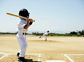 American boy wearing uniform of baseball playing the game
