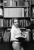 American broadcast journalist and media personality Barbara Walters dressed in a turtleneck sweater and jeans stands in front of a bookcase and looks...
