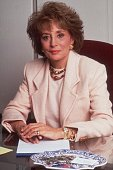American broadcast journalist Barbara Walters poses at a desk with a notepad and pen