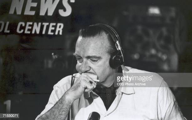 American broadcast journalist Walter Cronkite headphones on his head and a concerned look on his face rests his chin against his hand during coverage...