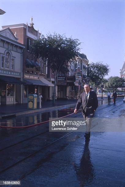 American businessman animator and director Walt Disney walks along a street in the Disneyland theme park Anaheim California 1964