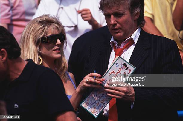 American businessman Donald Trump is handed an autograph book by his partner Marla Maples as they watch action on court as spectators during the 1991...