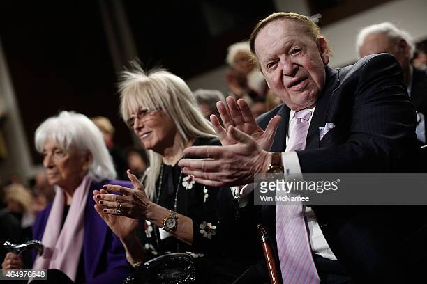 American businessman Sheldon Adelson applauds during a roundtable discussion on Capitol Hill with his wie Miriam Adelson and Marion Wiesel March 2...