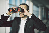 american businessman using binoculars in office