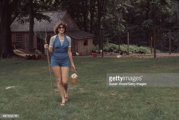 American businesswoman Martha Stewart carries a basket of eggs and a net as she walks the grounds of her home Westport Connecticut August 1976