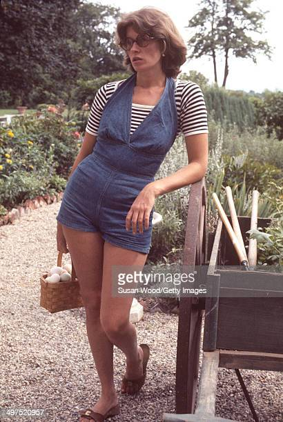 American businesswoman Martha Stewart carries a basket of eggs as she leans against a wheelbarrow on the grounds of her home Westport Connecticut...