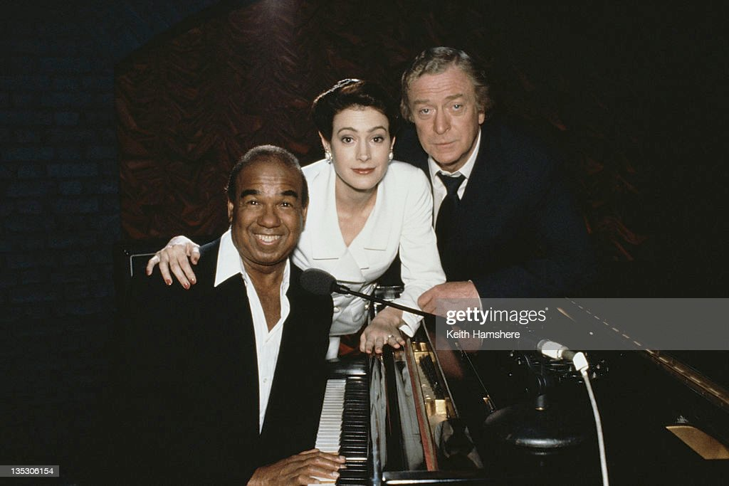 American cabaret singer and pianist Bobby Short (1924 - 2005), American actress Sean Young as Stacy Mansdorf and British actor Michael Caine as former secret agent Harry Anders in the film 'Blue Ice', 1992.