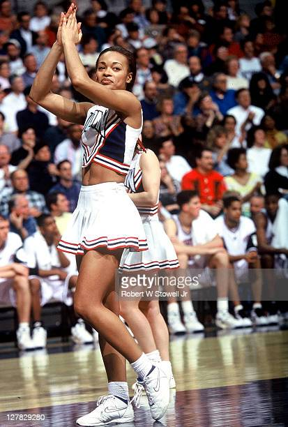 American cheerleader Alicia Ballenger of the University of Connecticut leads the crowd during a basketball game Hartford Connecticut 1996