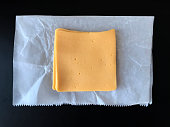 American Cheese on deli paper with black background.  iPhone