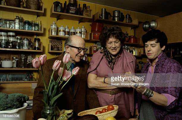 American chef author and television personality Julia Child and her husband Paul Cushing Child look at a small sculptutr held by an unidentified...