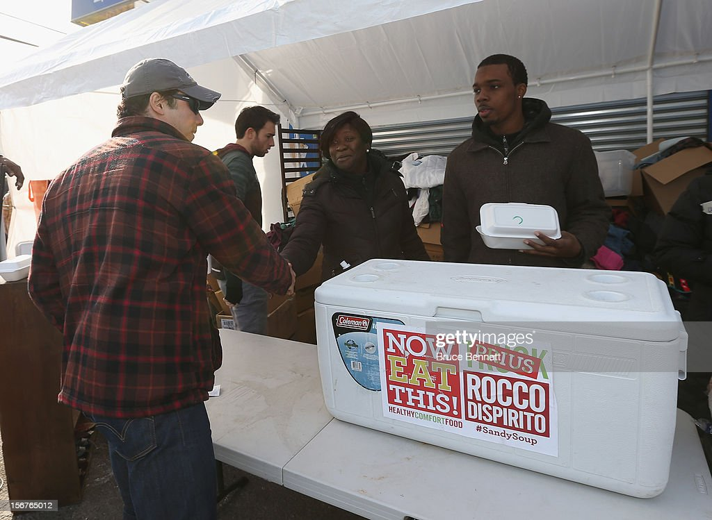 American chef Rocco DiSpirito hands off donated food to Sharon Plummer on Seagirt Boulevard on November 20, 2012 in Far Rockaway, Queens, New York. Dispirito whose food truck was destroyed in Superstorm Sandy delivered the food via Prius. Plummer has organized a group of volunteers and donations to assist the residents in the local community. More than three weeks after Superstorm Sandy hit the New York area, residents continue their restoration efforts in many affected areas in the New York region.