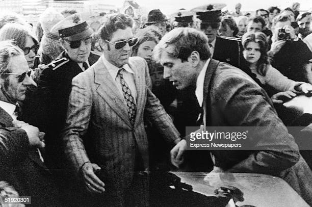 American chess champion and prodigy the controversial and tempermental Bobby Fischer exits a car into a waiting crowd which includes several...