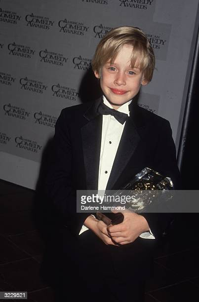 American child actor Macaulay Culkin smiles while holding an award in a tuxedo backstage at the American Comedy Awards Culkin won Funniest Actor in a...
