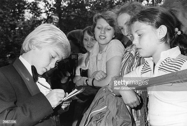 American child actor Ricky Schroder signs autographs for young female fans at the Royal Premiere of his first film the MGM production 'The Champ'...