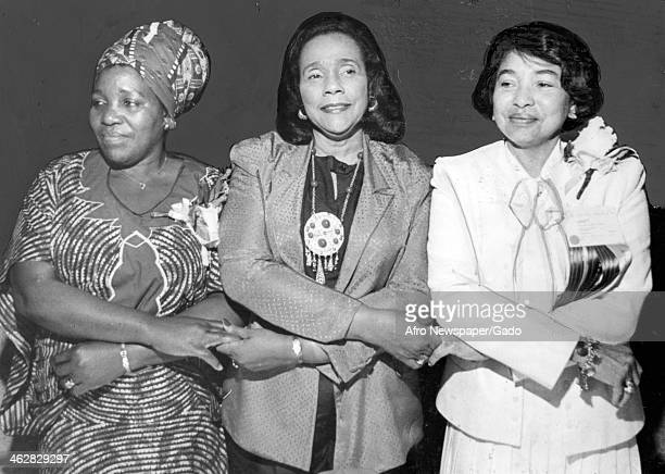 American Civil Rights activist Coretta Scott King stands arms crossed and holding hands with two unidentified women at an unspecified event August...