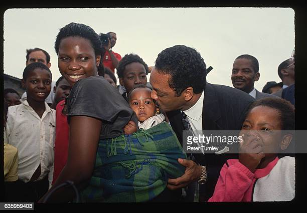 American civil rights activist Jesse Jackson kisses a baby during a visit to Soweto with antiApartheid leaders Jackson was visiting South Africa...