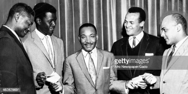 American Civil Rights and religious leader Dr Martin Luther King Jr smiles as he hands papers to a group of four men one of them is musician and...