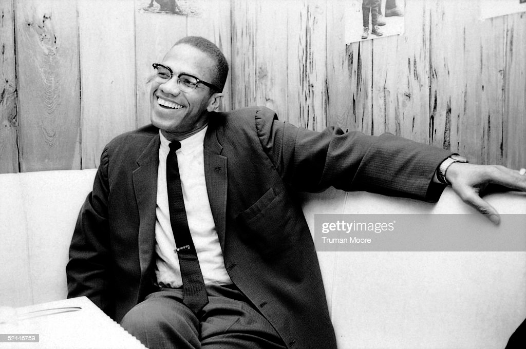 American civil rights leader Malcolm X laughs as he relaxes on a couch in a woodpanelled room March 1964