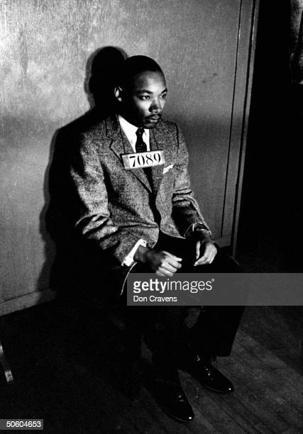 Rev Martin Luther King Jr director of segregated bus boycott with 7080 sign across his chest for police mug shot sitting on chair against wall in...