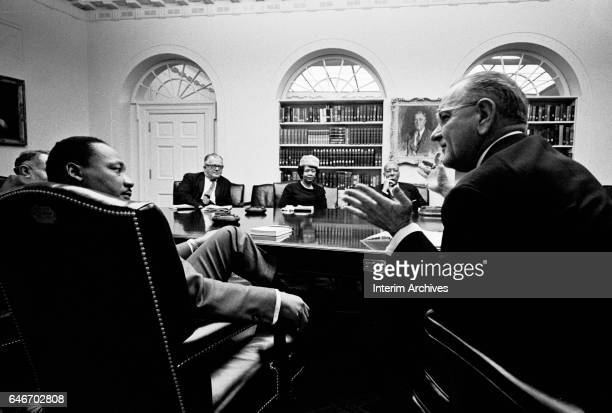 American Civil Rights leader Reverend Martin Luther King Jr listens to US President Lyndon Baines Johnson as they sit with others in the White...