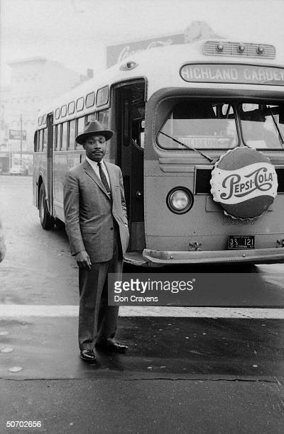 American Civil Rights leader Reverend Martin Luther King Jr stands in front of a bus at the end of the Montgomery bus boycott Montgomery Alabama...