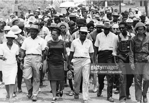 American Civil Rights leaders Dr Martin Luther King Jr and his wife Coretta Scott King lead an unidentified march with Reverend Ralph Abernathy and...