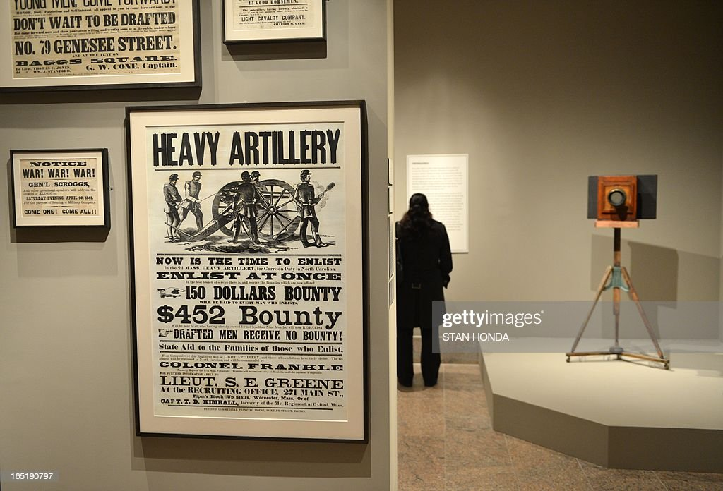 American Civil War-era enlistment posters (L) and 'Mathew B. Brady's Studio Camera and Tripod, 1860s' (R) in the exhibition, 'Photography and the American Civil War' April 1, 2013 at The Metropolitan Museum of Art in New York. AFP PHOTO/Stan HONDA