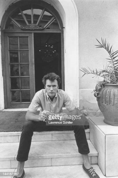 American Clint Eastwood eats a piece of chicken on the marble steps of an unidentified building Durango Mexico 1969 He was on a break during the...