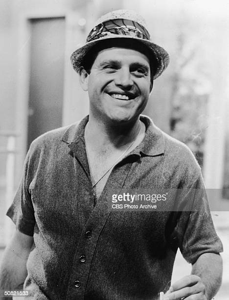 American comedian Alan King smiles wearing a straw hat while on a television set 1960s