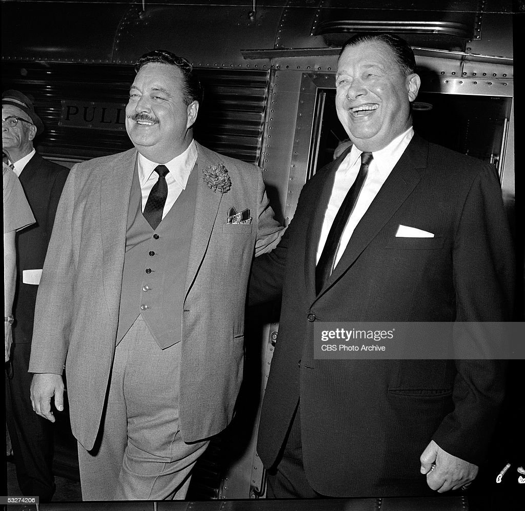 American comedian and actor Jackie Gleason (1916 - 1987) (left) and restauranteur Bernard Toots Shor (1904 - 1977) embrace in front of a train upon Gleason's arrival at Pennsylvania Station in New York, New York, August 18, 1962.