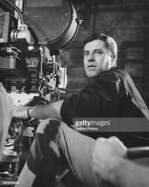 American comedian and actor Jerry Lewis next to a film camera on set circa 1960