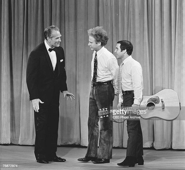 American comedian and actor Red Skelton chats with singing duo Art Garfunkel and Paul Simon on an episode of 'The Red Skelton Hour' August 22 1966