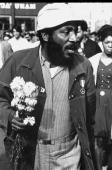 American comedian and social activist Dick Gregory holds a bouquet of flowers as he participates in a Civil Rights rally New York New York 1968