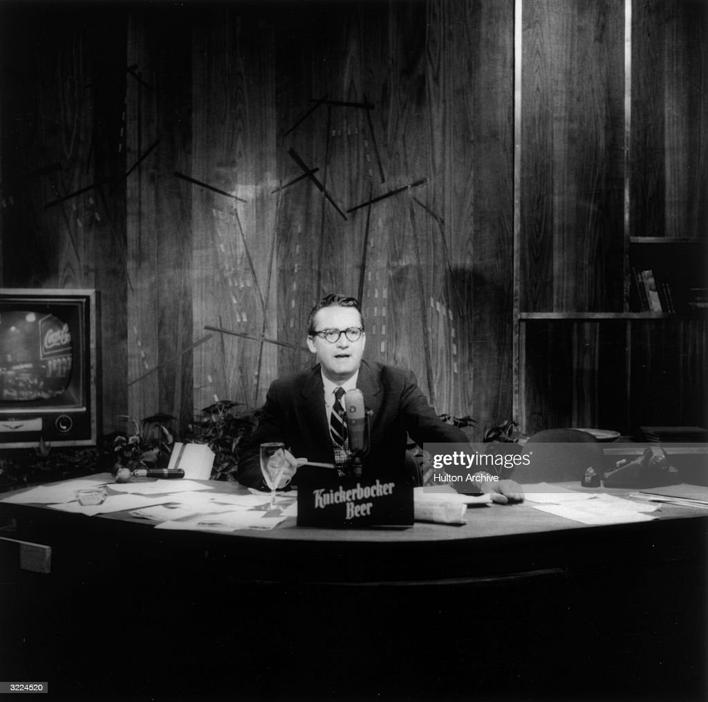 American comedian and talk show host Steve Allen (1921 - 2000) sitting at a desk speaking during an episode of 'The Tonight Show'. An advertisement for Knickerbocker beer is on his desk.