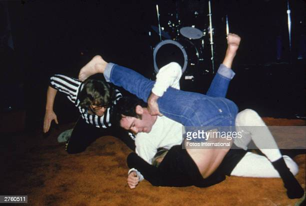 American comedian Andy Kaufman pins Elizabeth Hocker to the mat during a wrestling match as a referee gives the count at the Comedy Store nightclub...