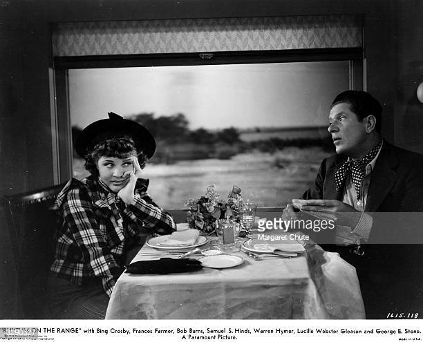 American comedian Bob Burns shares a meal with comedienne and vocalist Martha Raye in the dining car of a train in a scene from their debut film...