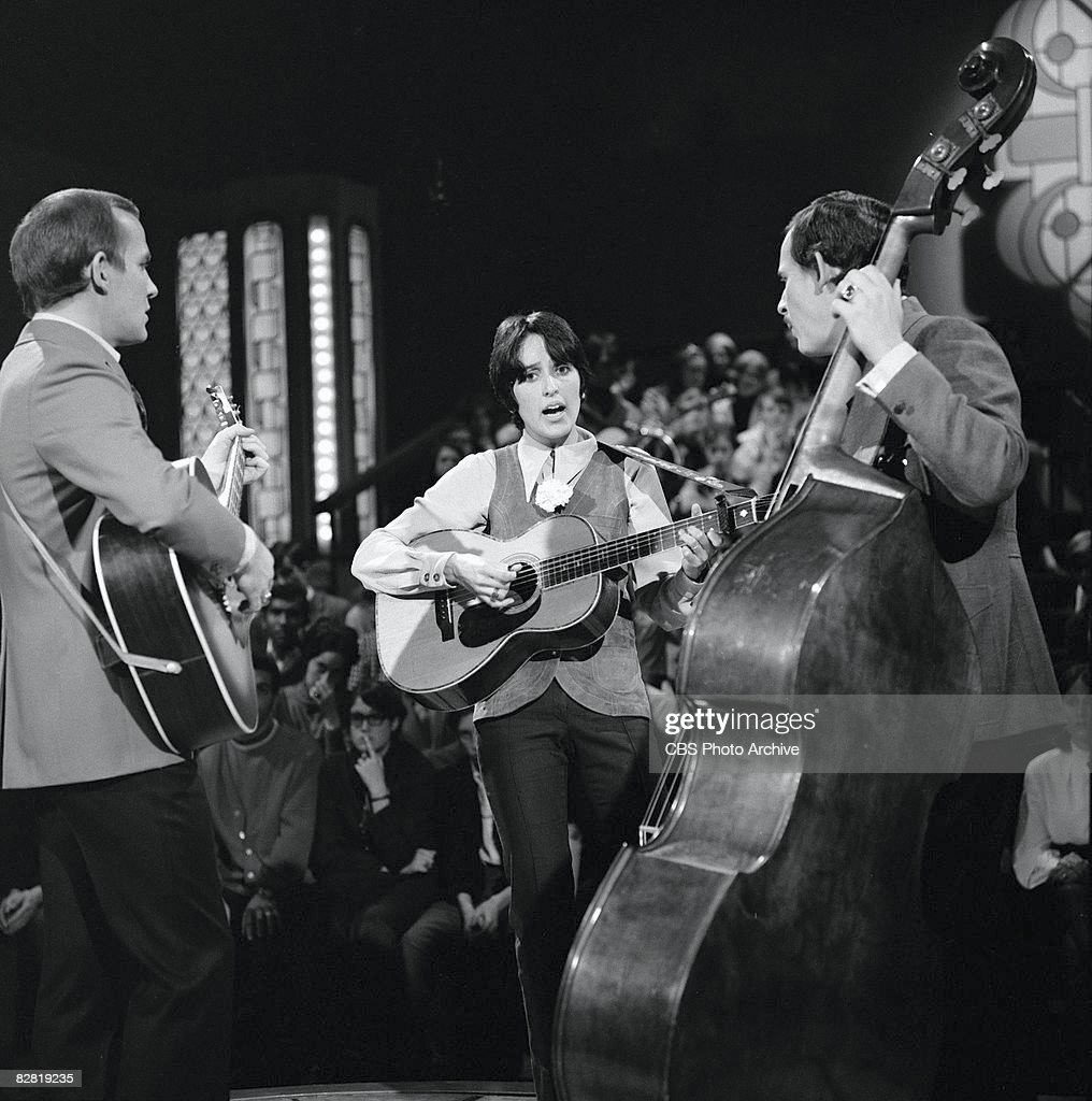 American comedian musician brothers Tom Smothers (left) and Dick Smothers (right) perform with American folk singer Joan Baez during the taping of an episode of the television comedy and variety show, 'The Smothers Brothers Comedy Hour,' Los Angeles, California, March 2, 1969. The episode was originally broadcast on March 30, 1969.