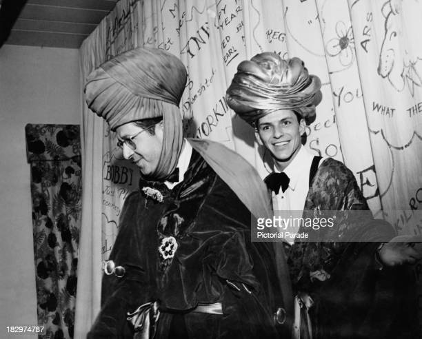 American comedian Phil Silvers and actor and singer Frank Sinatra in fancy dress costumes for a New Year's Eve party 31st December 1947
