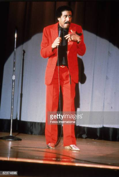 American comedian Richard Pryor wears a bright red suit as he performs a standup act for his 'Live on Sunset Strip' special Los Angeles California...