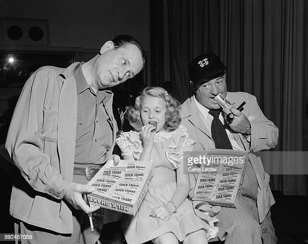 American comedians Bud Abbott and Lou Costello share boxes of 'Milk Shake' brand candy bars with an unidentified young girl during a commercial...