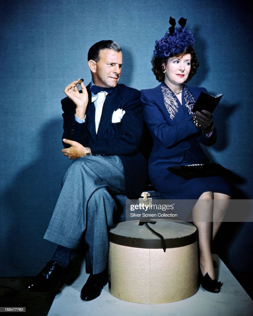 American comedians George Burns and his wife Gracie Allen circa 1940 The couple are sitting on a suitcase with Burns smoking a cigar and Allen...