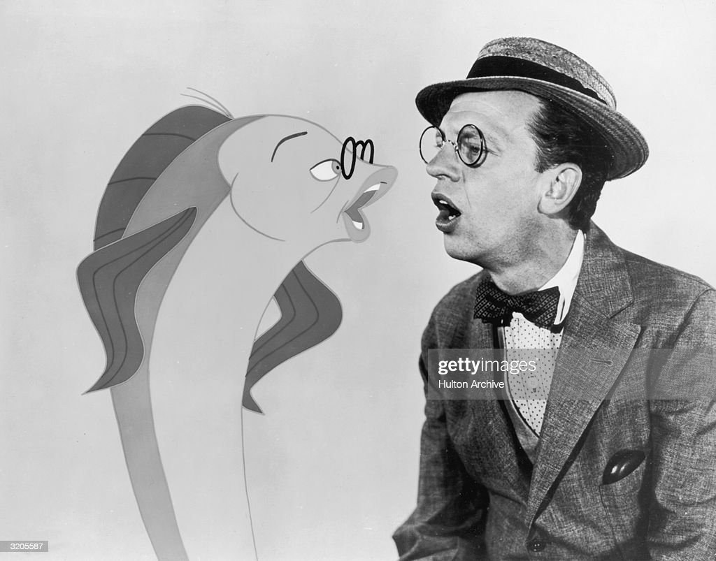 American comedic actor Don Knotts talks to an animated fish version of himself in a still from director Arthur Lubin's film, 'The Incredible Mr. Limpet'. He and the fish wear pince-nez eyeglasses. Knotts wears a straw hat and a bow tie.