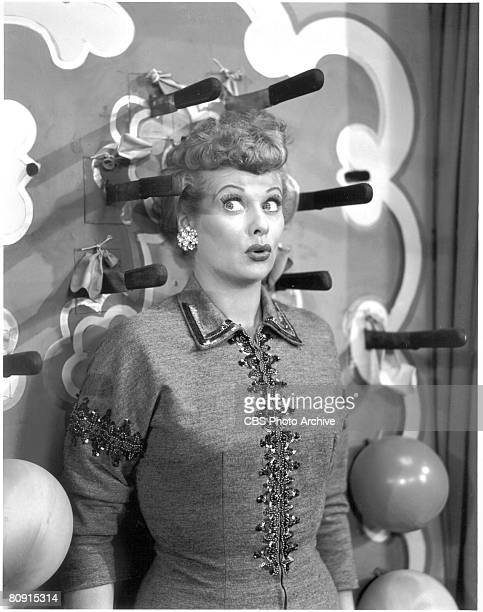 American comedienne and actress Lucille Ball looks worredly at the knives that surround her head on an episode of 'I Love Lucy' entitled 'Lucy Tells...