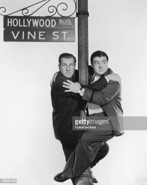American comedy team Bud Abbott and Lou Costello cling to a 'HOLLYWOOD BLVD/VINE ST' sign pole in a promotional portrait for director S Sylvan...