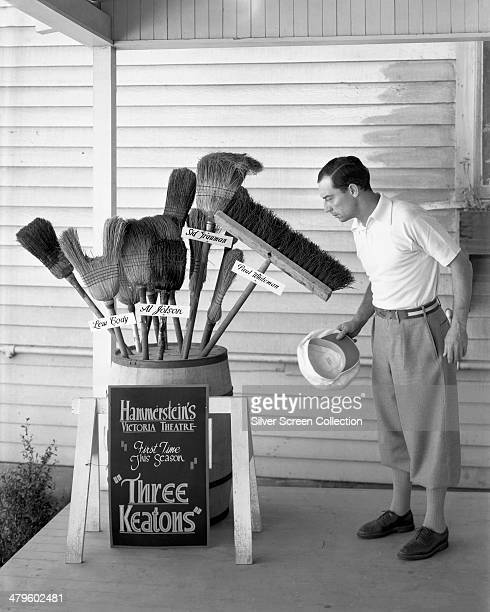 American comic actor and filmmaker Buster Keaton inspects a barrel full of brooms circa 1930 The brooms are labelled with the names of actors Lew...