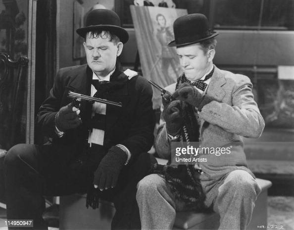 American comic actors Stan Laurel and Oliver Hardy examining handguns in a scene from one of their films circa 1935