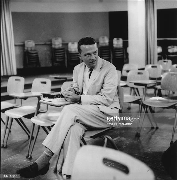 American composer and artist George Brecht sits at a student's desk in a classroom at the New School New York New York August 5 1959 At the time...