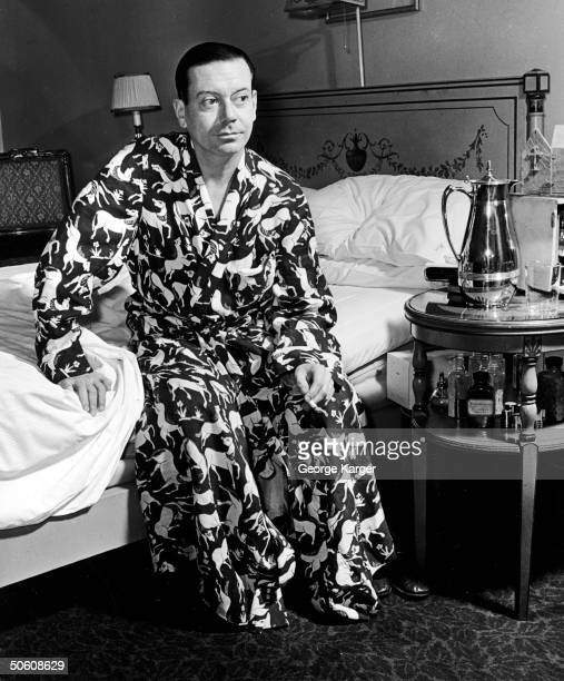 American composer Cole Porter sits on edge of bed in his room at the Ritz Hotel a cigarette in his hand and dressed in a robe with a wild horse print...