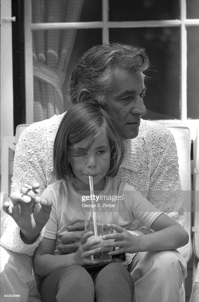 American composer Leonard Bernstein (1918 - 1990) sits with his daughter Nina on his lap during his 50th birthday celebration in Connecticut, 1968. Nina is sipping a drink through a straw.