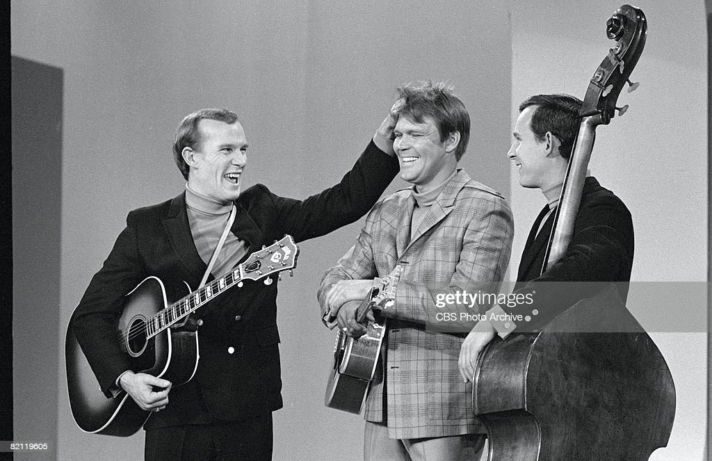American country and pop musician Glen Campbell (center) laughs as comedian and musician Tom Smothers (left) ruffles his hair while Dick Smothers looks on during an episode of 'The Smothers Brothers Comedy Hour,' February 23, 1968.